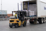 small yellow fork lift pulls pallets of food packages off a large delivery truck