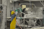 person in yellow protective gear and safety helmet washing down food manufacturing equipment
