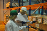 man and women in white coats and safety helmets inspect packages of food