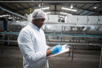 man in blue gloves, white coat, and hairnet making notes on clipboard inside food manufacturing facility