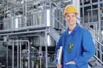 man in yellow safety helmet and blue jacket stands in front of food manufacturing equipment